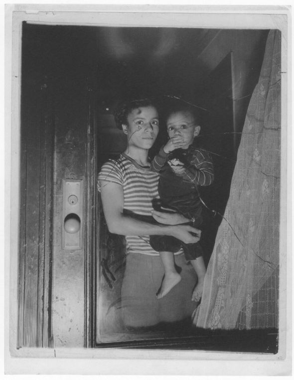 Bernice Lythcott and her one-year-old son Leonard look out a window through which hoodlums threw stones, 1943