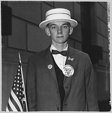 Diane Arbus - A boy with a straw hat and flag waiting to march in a pro-war parade, 1967