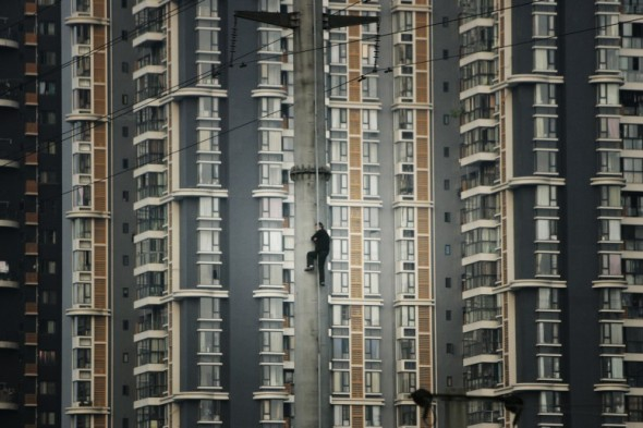 Shaofeng Xu - Un hombre escala por una torre de electricidad de alto voltaje en Ghengdu, Sichuán, China. Quería llamar la atención por el hecho de que no había recibido compensación alguna del gobierno por la demolición de su casa.